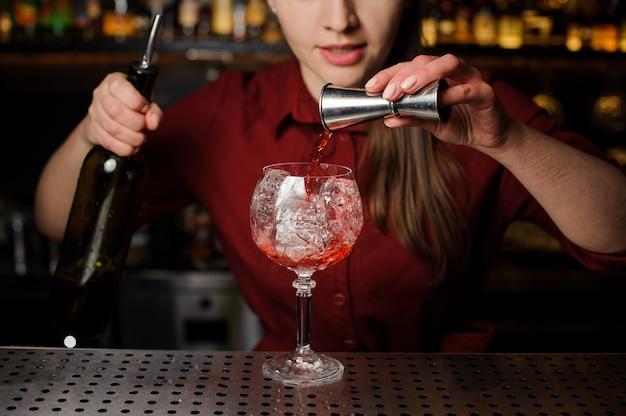Kobieta barman nalewanie gorzki do szklanki do robienia koktajlu strzykawki aperol