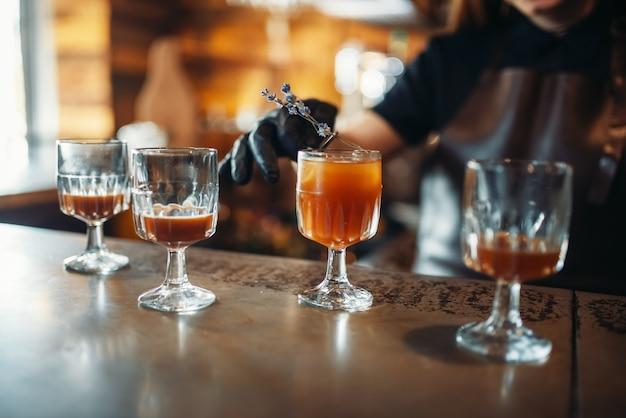 Kobieta barman przygotowuje koktajl alkoholowy w pubie