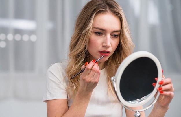 Kobieta barwienia usta pędzlem