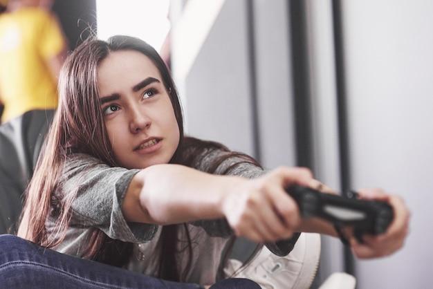 Kobieta bawi się na konsoli i trzyma joystick w rękach