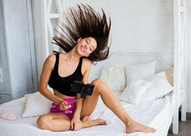 Kobieta bawi się włosami i robienia zdjęć