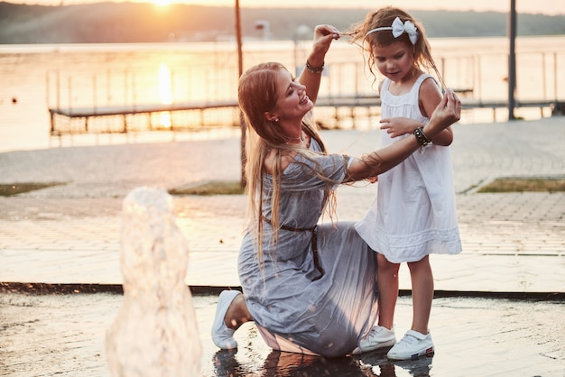 Kobieta bawi się z dzieckiem w pobliżu oceanu w parku o zachodzie słońca