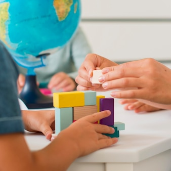 Kobieta bawi się z małymi dziećmi podczas zajęć