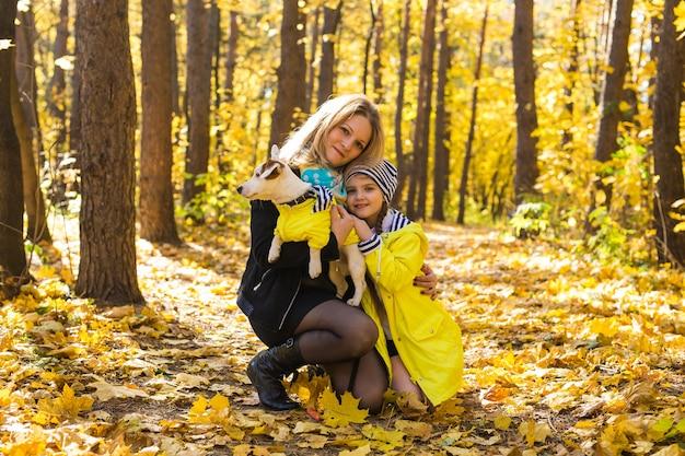 Kobieta bawi się z psem w parku jesień