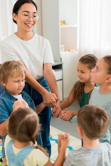 Kobieta bawi się ze swoimi uczniami w pomieszczeniu