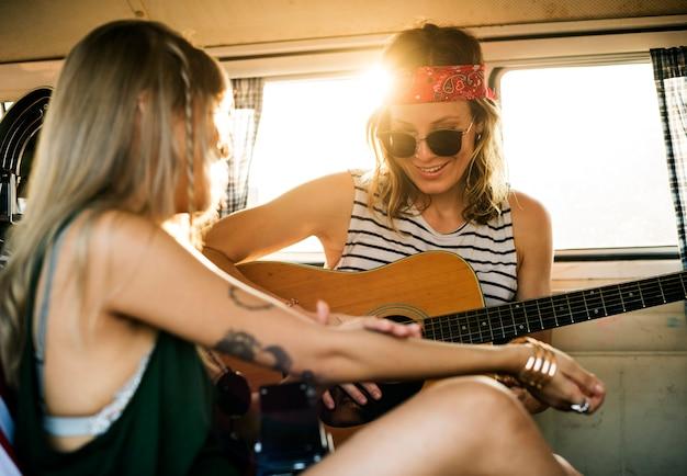 Kobieta bawić się gitarę na wycieczce samochodowej z przyjaciółmi wpólnie