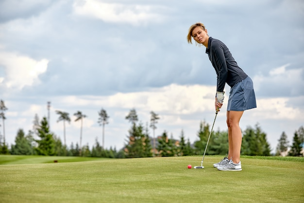 Kobieta bawić się golfa na zieleni polu