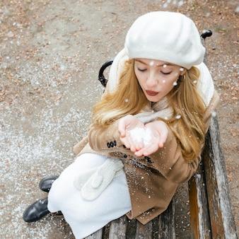 Kobieta bawić się śniegiem na ławce w zimie