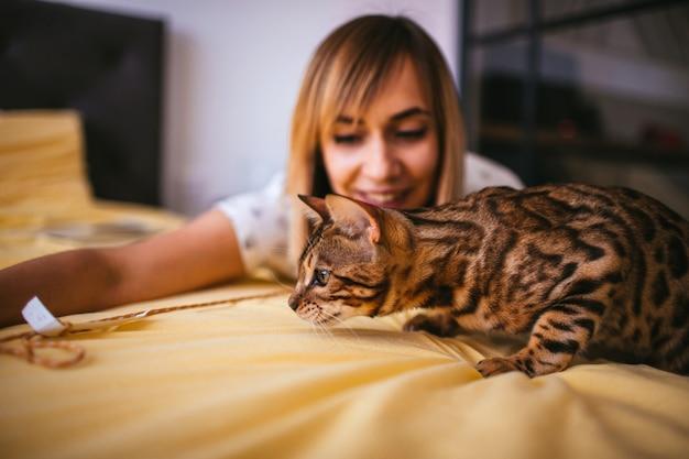 Kobieta bawić się z arkaną z bengalia kotem