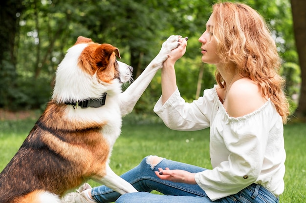 Kobieta bawić się z jej najlepszym przyjacielem w parku