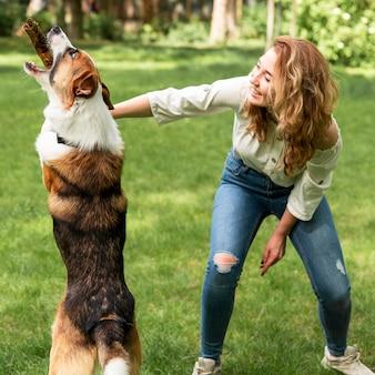Kobieta bawić się z jej psem w parku