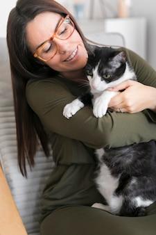 Kobieta bawić się z kota obsiadaniem na krześle