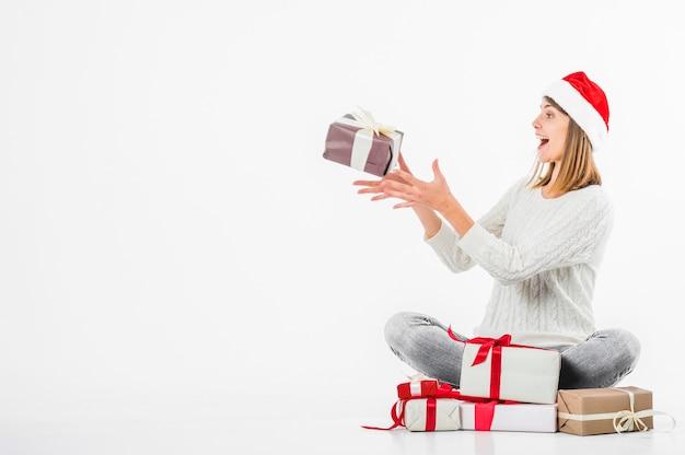 Kobieta bawić się z prezenta pudełkiem na podłoga