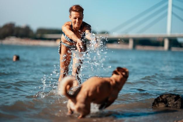 Kobieta bawić się z psem w rzece i bryzga wodę