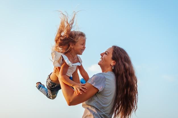 Kobieta bawić się zabawę z córką w wiosna parku i