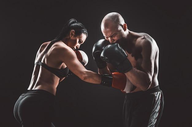 Kobieta bez koszuli ćwiczy z trenerem na lekcji boksu i samoobrony walka kobiet i mężczyzn