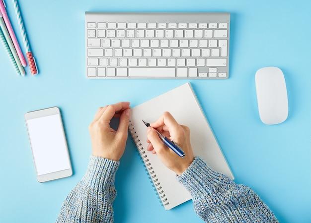 Kobieta bez twarzy pisze w notatniku. telefon komórkowy z pustym białym ekranem.