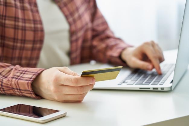 Kobieta bez twarzy płacąca kartą debetową podczas robienia zakupów w internecie na laptopie