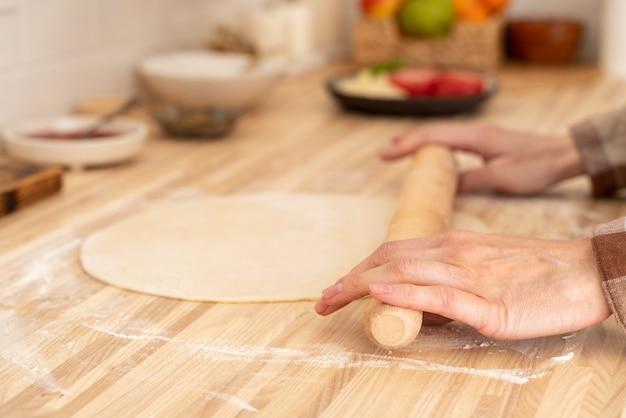 Kobieta bez twarzy rozwałkowuje ciasto wałkiem na kuchennym stole w domu,