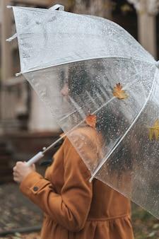 Kobieta bez twarzy, trzymając parasol na zewnątrz w parku jesienią podczas deszczu.