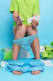 Kobieta bez twarzy w codziennych ubraniach trzyma podpaskę higieniczną, a tampon bawełniany ma miesiączkę