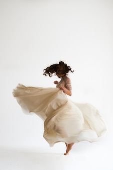 Kobieta biała sukienka, modelka w długiej jedwabnej sukni, macha latanie tkaniny
