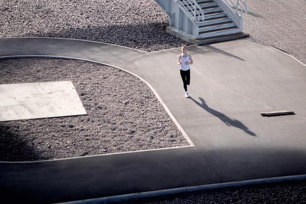 Kobieta biega na bieżni po ulicy oświetlonej promieniami słońca