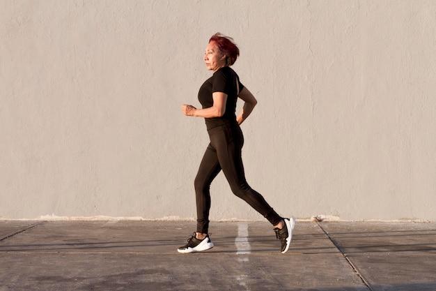 Kobieta biega outdoors bocznego widoku strzał