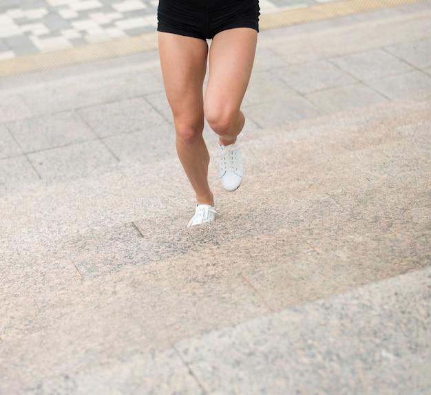 Kobieta biega w górę schodka niskiego kąta strzału