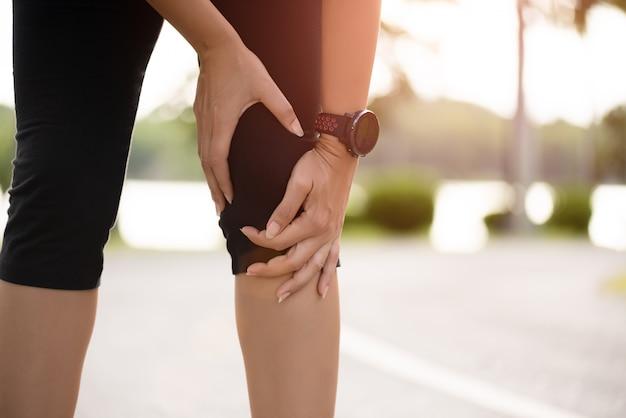Kobieta biegacz czuje ból na kolanie w parku.