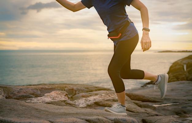 Kobieta biegacz działa na kamiennej plaży nad morzem rano z wschodem słońca. sprawny i silny zdrowej kobiety trening na świeżym powietrzu. dopasowana dziewczyna nosi elegancki pasek i torbę. kobieta działa.