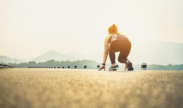Kobieta biegacz na butach drogowych jest gotowa opuścić punkt wyjścia.