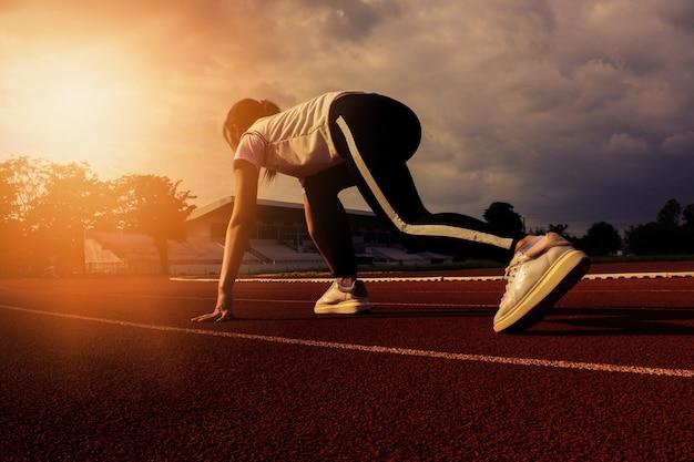 Kobieta biegacz na początku wyścigu. i stworzyć zdrowych sportowców do pracy.