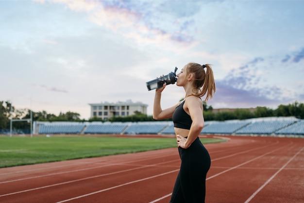 Kobieta biegacz pije wodę, trenując na stadionie