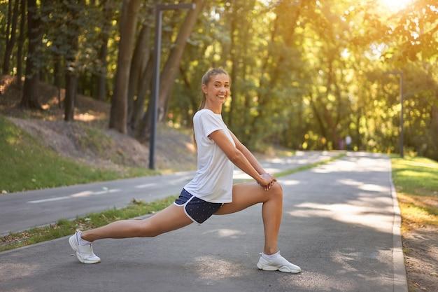 Kobieta biegacz rozciąganie nóg przed ćwiczeniami w parku latem rano