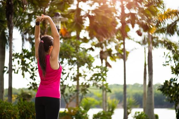Kobieta biegacz rozciąganie ramienia przed uruchomieniem w parku. koncepcja ćwiczeń na świeżym powietrzu.