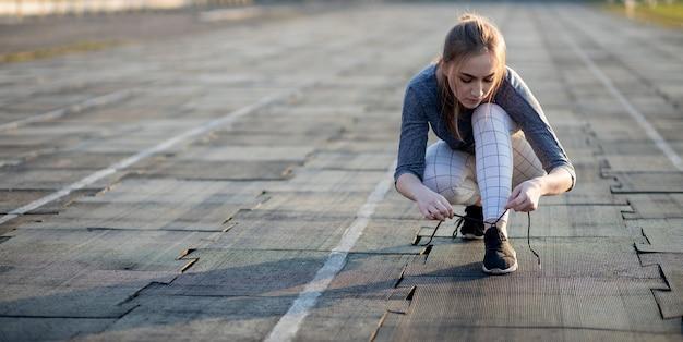 Kobieta biegacz sznurowanie jej trampki na bieżni stadionu.