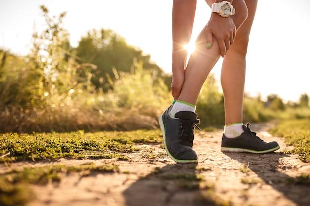 Kobieta biegacz trzymać jej sport kontuzji nogi