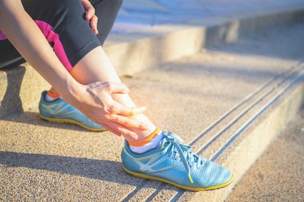 Kobieta biegacz trzymać jej sport rannych kolana na zewnątrz