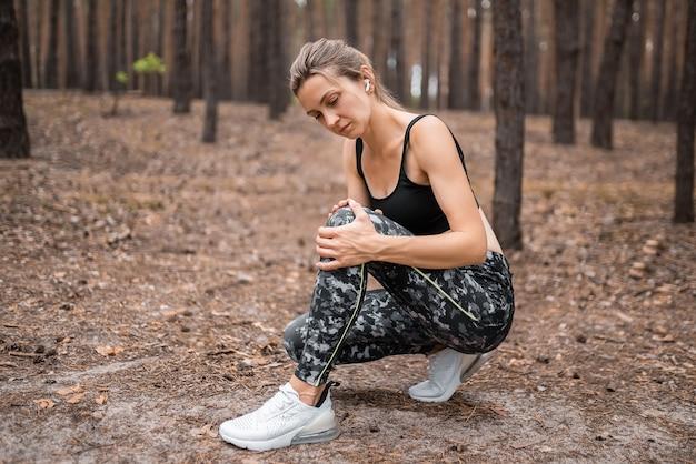 Kobieta biegacz trzymać jej sportowe kontuzjowane kolano.