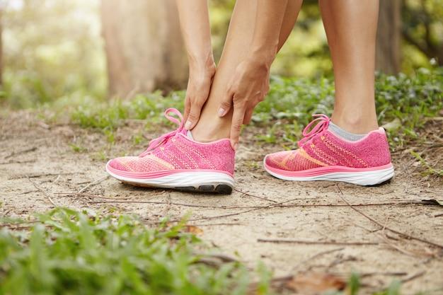 Kobieta biegacz trzymając skręconą kostkę po uruchomieniu ćwiczeń na świeżym powietrzu.
