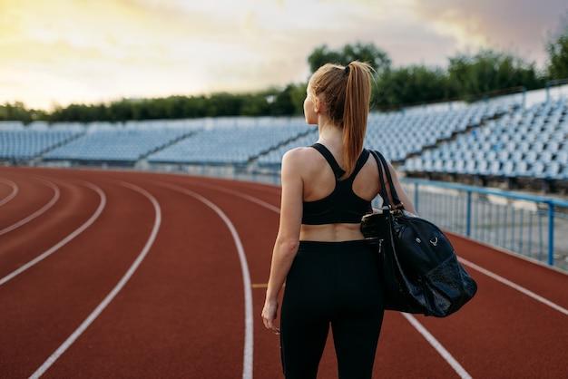 Kobieta biegacz w odzieży sportowej trzyma torbę sportową, widok z tyłu, trening na stadionie. kobieta robi ćwiczenia rozciągające przed uruchomieniem na arenie na świeżym powietrzu