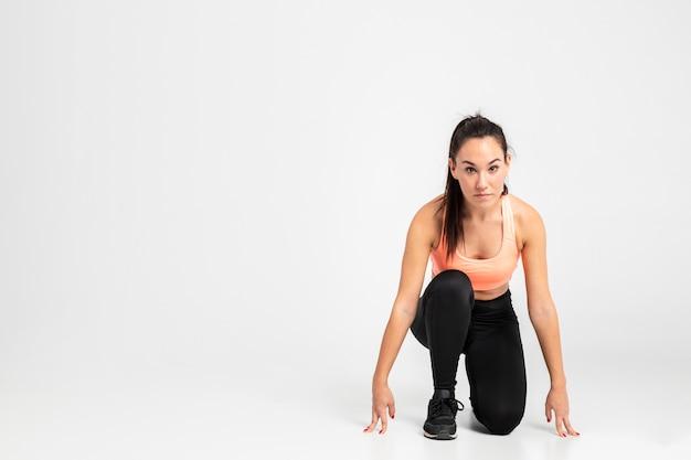 Kobieta biegacz w pozycji początkowej z miejsca na kopię