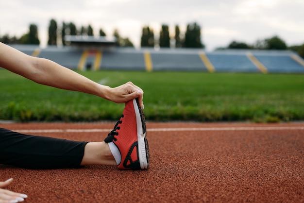 Kobieta biegaczka w odzieży sportowej, trening na stadionie. kobieta robi ćwiczenia rozciągające przed bieganiem na arenie na świeżym powietrzu
