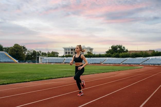 Kobieta biegaczka w sportowej joggingu, trening na stadionie. kobieta robi ćwiczenia rozciągające przed bieganiem na arenie na świeżym powietrzu
