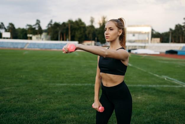 Kobieta biegaczka w sportowej posiada hantle, trening na stadionie. kobieta robi ćwiczenia rozciągające przed bieganiem na arenie na świeżym powietrzu