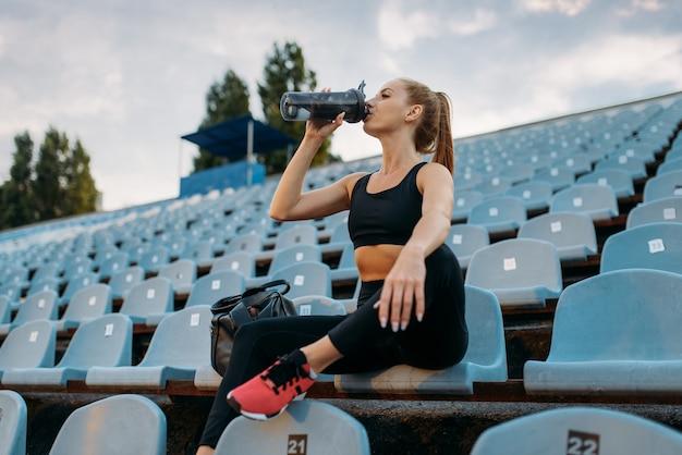 Kobieta biegaczka w sportowej siedzi na trybunie i pije wodę, trening na stadionie. kobieta robi ćwiczenia rozciągające przed bieganiem na arenie na świeżym powietrzu