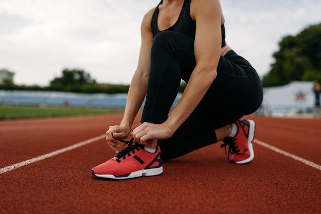 Kobieta biegaczka w sportowej wiązanie jej sznurowadeł, trening na stadionie. kobieta robi ćwiczenia rozciągające przed bieganiem na arenie na świeżym powietrzu