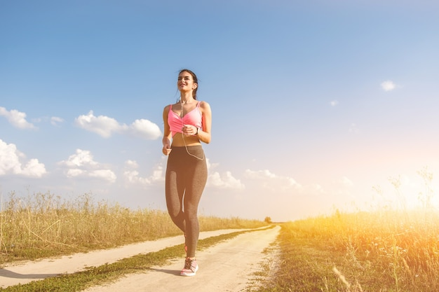 Kobieta biegająca po polnej drodze na słonecznym tle