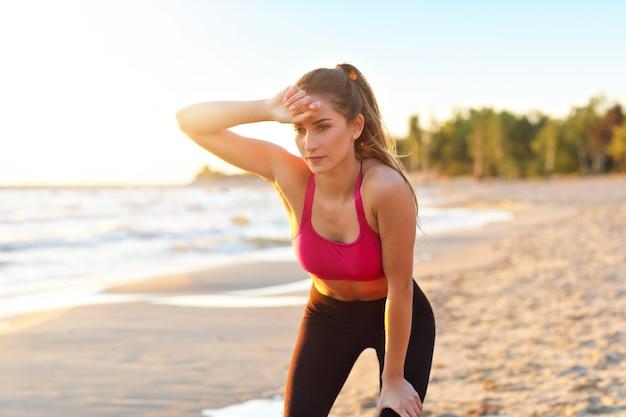Kobieta biegająca samotnie o pięknym zmierzchu po plaży